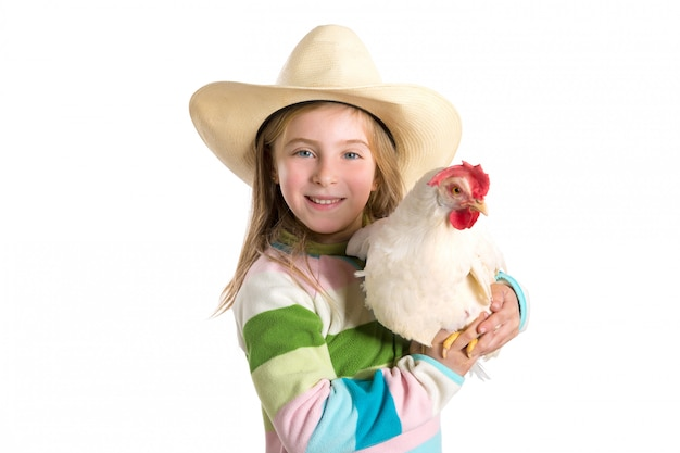Fazendeiro de garota garoto loiro segurando a galinha branca nos braços