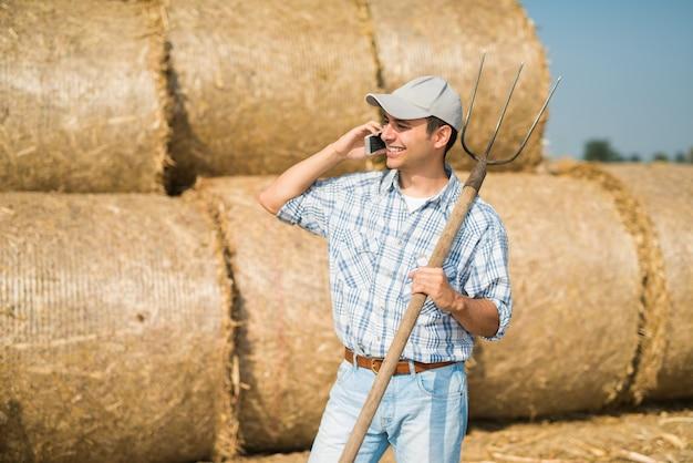 Fazendeiro de sorriso que fala no telefone quando no campo