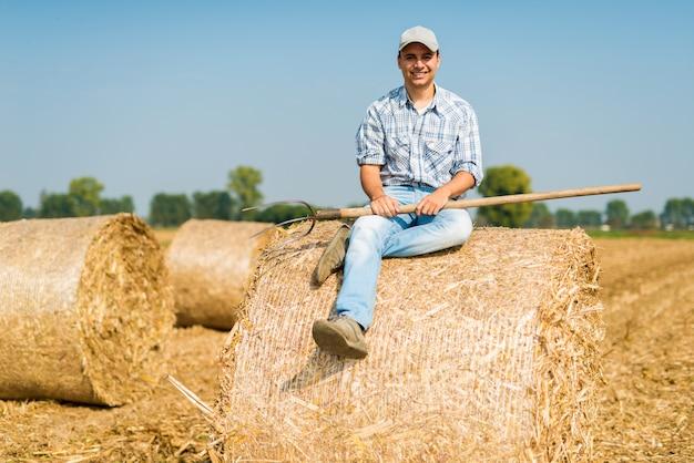 Fazendeiro de sorriso que relaxa no feno em seu campo