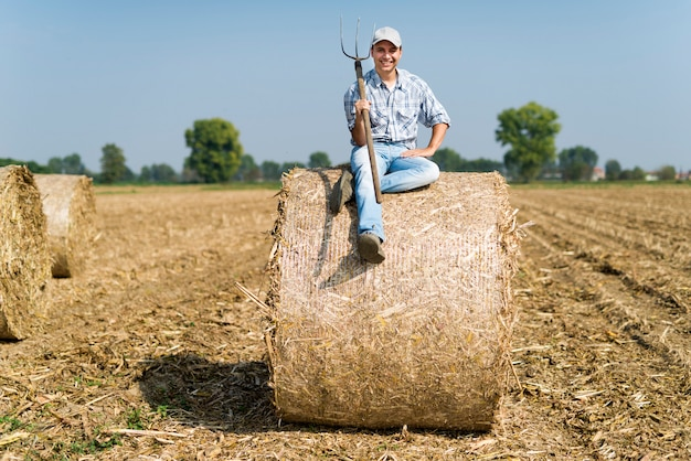 Fazendeiro de sorriso que senta-se em um pacote de feno em seu campo