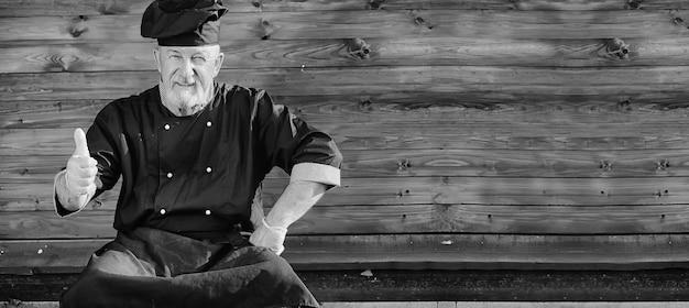 Fazendeiro de uniforme com legumes frescos em um bacground de madeira