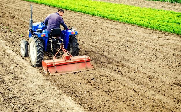 Fazendeiro dirige um trator com uma fresadora