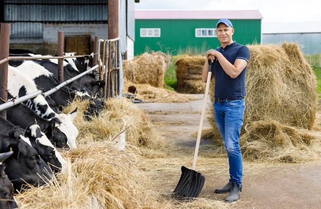 Fazendeiro em fazenda com vacas leiteiras