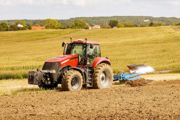 Fazendeiro em um grande trator vermelho preparando terreno com arado para a semeadura