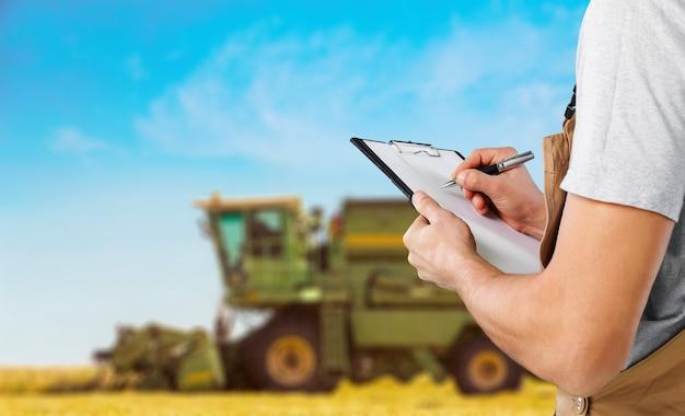Fazendeiro escrevendo em um clipe de papel no fundo
