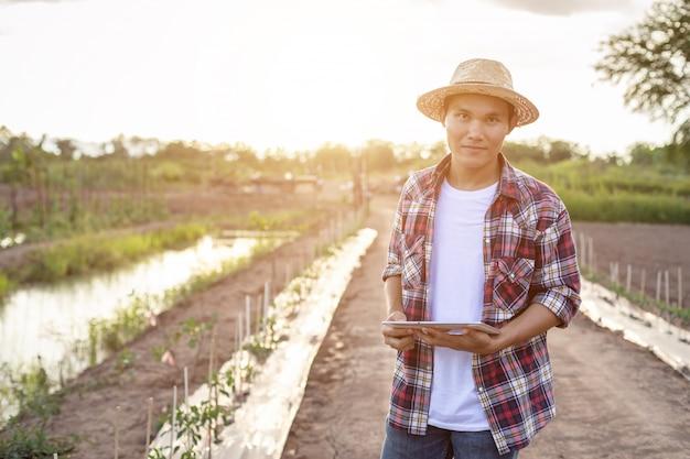 Fazendeiro esperto asiático que guarda a tabuleta em sua exploração agrícola orgânica.