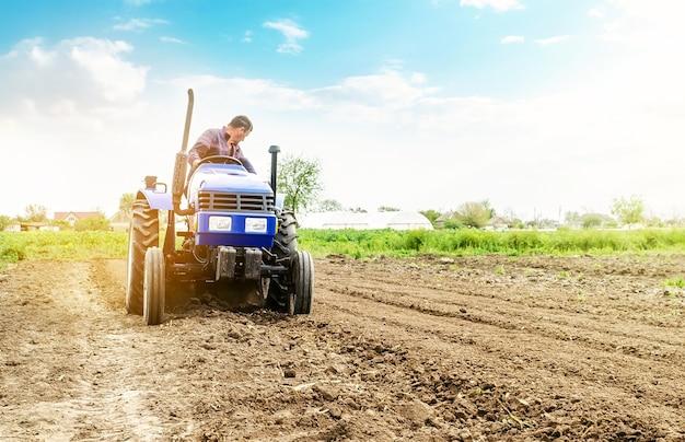 Fazendeiro está processando solo em um trator.