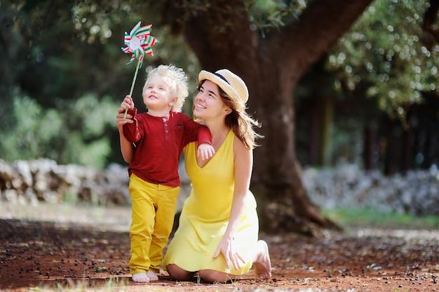 Fazendeiro fêmea feliz e seu ajudante pequeno que trabalham no bosque verde-oliva em itália.