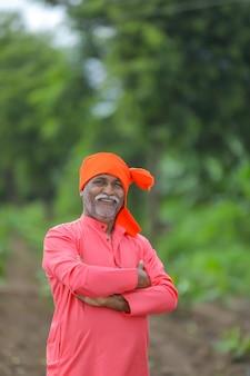 Fazendeiro indiano feliz em pé e sorrindo para o campo