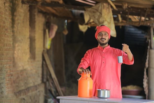 Fazendeiro indiano ou leiteiro coletando leite em fazenda de gado leiteiro