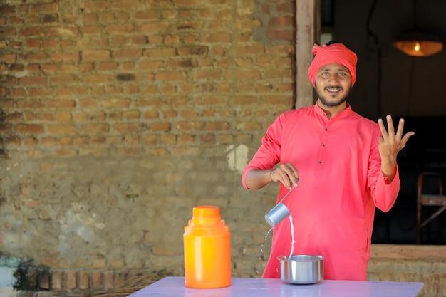 Fazendeiro indiano ou leiteiro distribui leite em fazenda de gado leiteiro