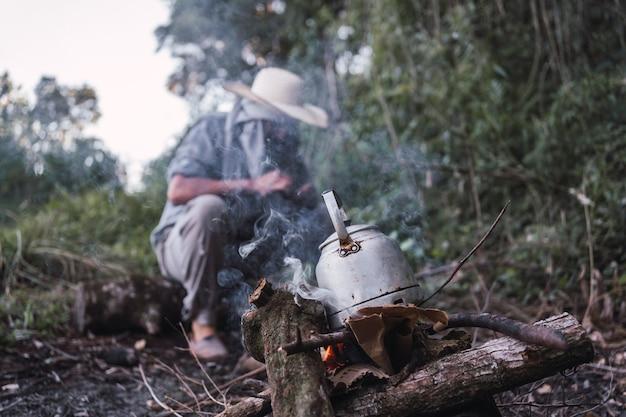 Fazendeiro local fazendo fogo para aquecer água em uma chaleira rústica.