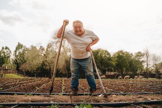 Fazendeiro mais velho, na casa dos 50 anos, aproveitando seu trabalho e sua vida nos campos, agarrando uma enxada após remover o solo.