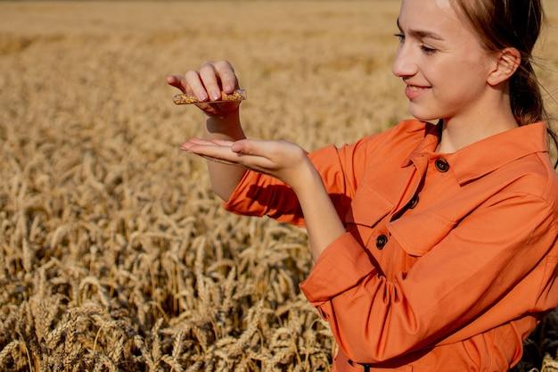 Fazendeiro pesquisando planta no campo de trigo. em sua mão, ele segura um tubo de vidro contendo substância de teste com tablet digital. agricultura inteligente usando tecnologias modernas no conceito de agricultura e cientista.