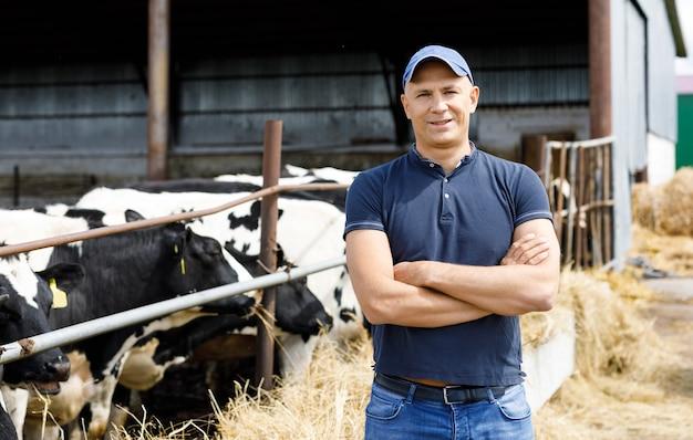Fazendeiro positivo com vacas na fazenda