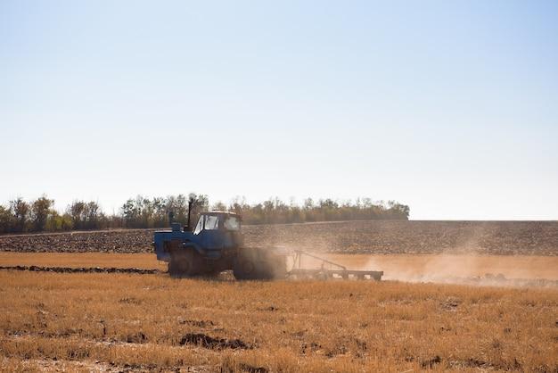 Fazendeiro preparando seu campo em um trator pronto para a primavera.
