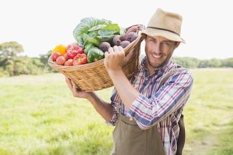 Fazendeiro que transporta cesta de produtos hortícolas