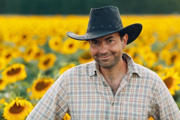 Fazendeiro sorrindo e parado em um campo de girassol
