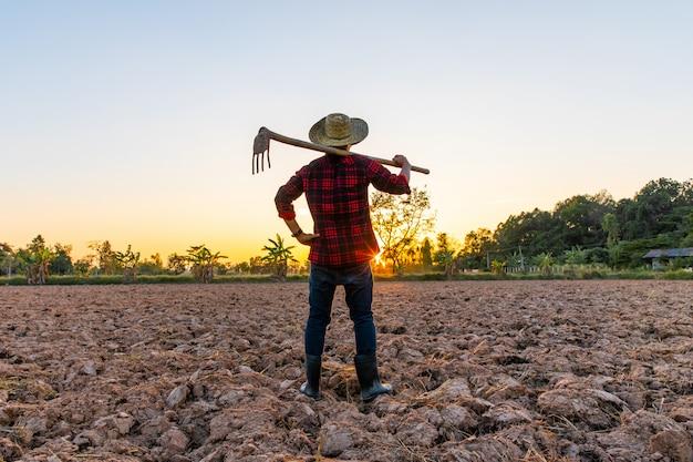 Fazendeiro trabalhando no campo ao pôr do sol ao ar livre