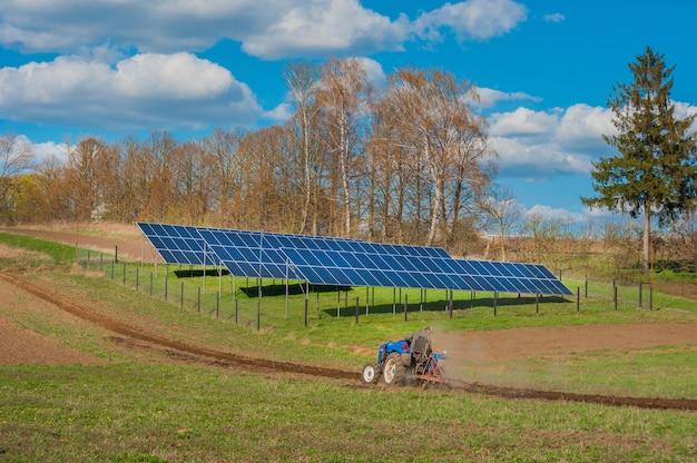 Fazendeiros arando trator, trabalho de primavera no campo e painel solar com céu nublado