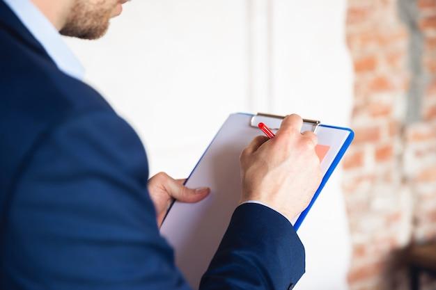 Fazendo anotações das tarefas diárias sentado na mesa jovem gerente retorna ao trabalho na quarentena do escritório