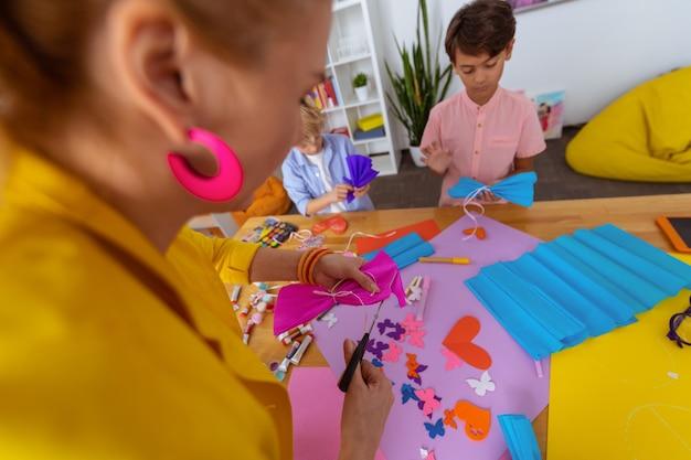 Fazendo arco de papel. professor usando uma tesoura enquanto faz um laço de papel rosa enquanto fica perto dos alunos