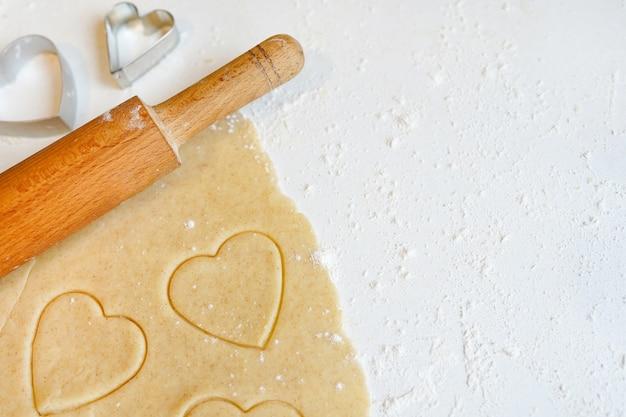 Fazendo biscoitos caseiros em forma de coração com massa crua de gengibre - biscoitos caseiros festivos para o dia dos namorados