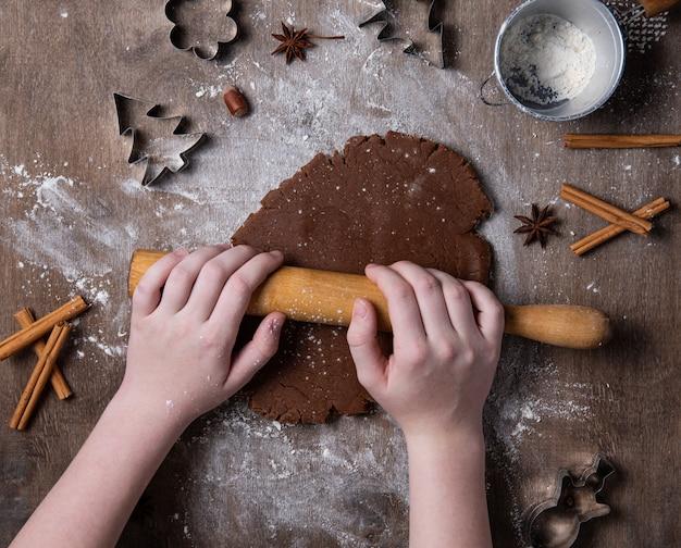 Fazendo biscoitos de gengibre de natal chocolate com as mãos na mesa velha.