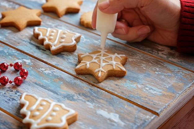 Fazendo biscoitos de gengibre de natal com decoração de esmalte branco