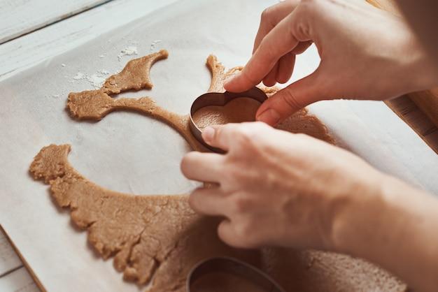 Fazendo biscoitos de gengibre em forma de coração para dia dos namorados. mão de mulher usar cortador de biscoitos. conceito de comida de férias