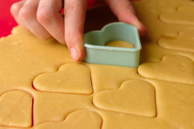 Fazendo biscoitos de gengibre em formato de coração usando um cortador de plástico na esteira vermelha de silicone