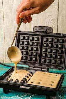 Fazendo bolachas em casa. derramando a massa no ferro de waffle