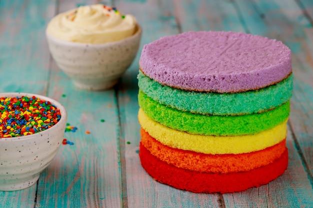 Fazendo bolo de aniversário em camadas de arco-íris colorido na mesa de madeira.