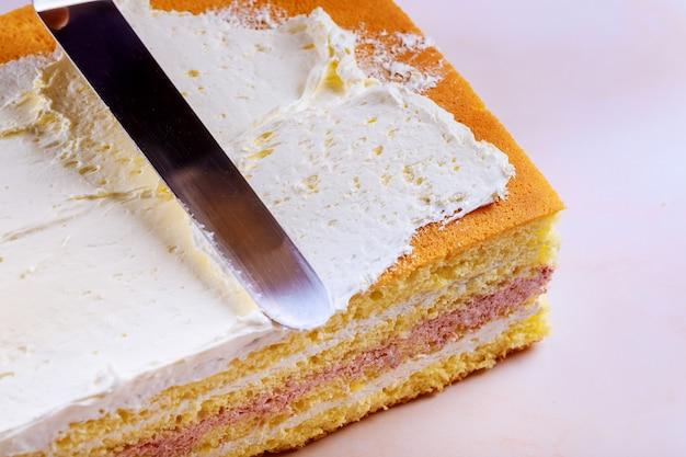 Fazendo bolo de camada de biscoito com creme branco, usando uma espátula de cozinha