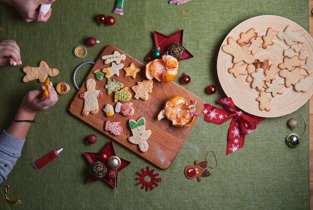 Fazendo boneco de gengibre, massa de biscoito. o conceito de uma festa em casa, um jantar em família. conceito de tradições de ano novo e processo de cozimento. cookies na mesa verde de madeira.