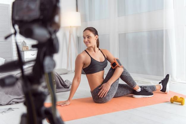 Fazendo bons exercícios. mulher jovem atlética de cabelos escuros com ótimo conteúdo, sorrindo e fazendo exercícios para as costas enquanto está sentada no tapete e fazendo um vídeo para seu blog