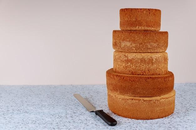 Fazendo camada de bolo de casamento de tamanhos diferentes, bolos de esponja na mesa