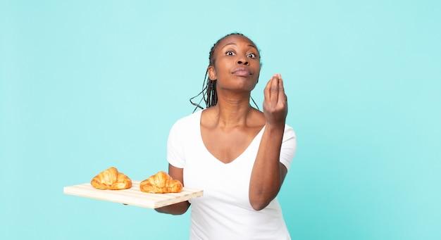 Fazendo capice ou gesto de dinheiro, dizendo para você pagar e segurando uma bandeja de croissant