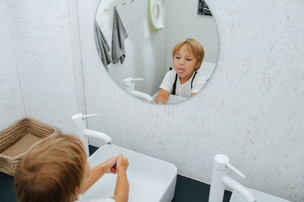 Fazendo careta no espelho, garotinho lavando as mãos na pia do banheiro