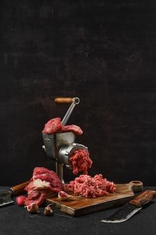 Fazendo carne bovina picada com moedor de carne antiquado