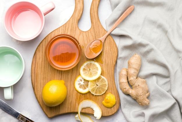 Fazendo chá com limão e gengibre em uma placa de madeira