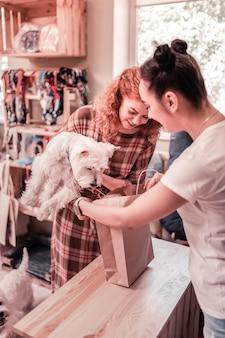 Fazendo compras com cachorro. mulher cacheada segurando seu cachorro branco e fofo enquanto faz compras em um pet shop