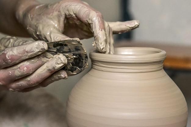 Fazendo crock close-up molhado bruto. mãos de homem e ferramenta para fazer macro de jarro de argila. o escultor na oficina faz uma jarra com um close de argila. vaso de argila branca crua úmida closeup,