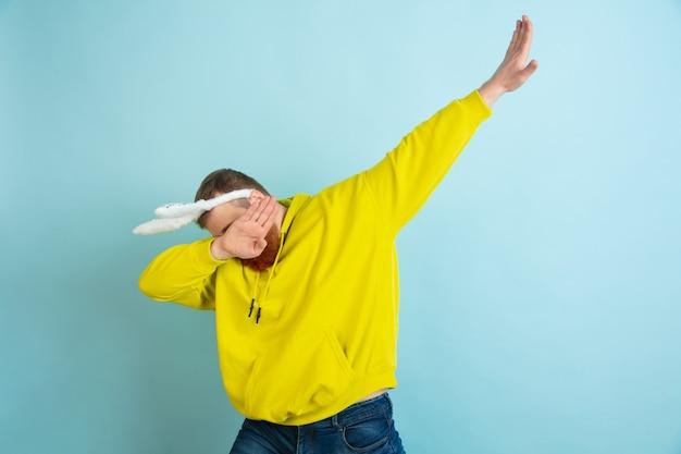 Fazendo dab. homem caucasiano como um coelhinho da páscoa com roupas casuais brilhantes sobre fundo azul do estúdio. saudações de páscoa feliz. conceito de emoções humanas, expressão facial, feriados. copyspace.