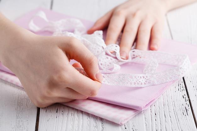 Fazendo decorações de mesa. uma foto de mulher costurando uma toalha de mesa de linho bege natural, toalhas e guardanapos com estampa de rosas e uma guarnição de renda de linho branco de crochê, usando agulhas