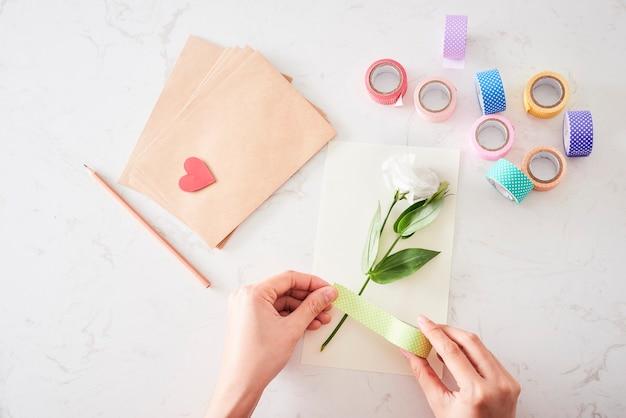Fazendo decorações ou cartões. tiras de papel, flores, tesouras. artesanato feito à mão nas férias: aniversário, dia das mães ou pai, 8 de março, casamento.