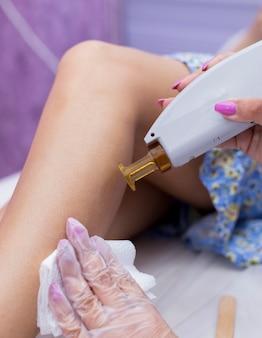 Fazendo depilação a laser na pele de pernas femininas.