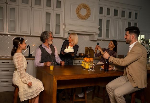 Fazendo desejo família comemorando aniversário do avô avó trazer bolo com velas