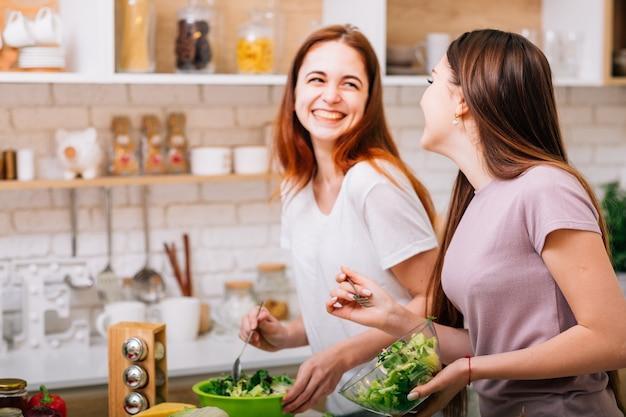 Fazendo dieta juntos. diversão de culinária feminina. duas mulheres jovens com tigelas de salada rindo alto.