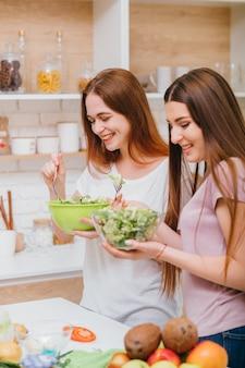 Fazendo dieta juntos. diversão de culinária jovem feminino. duas mulheres atraentes com tigelas de salada. sorrindo, se divertindo.